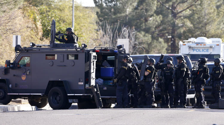 Members of the Phoenix Police Department SWAT team prepare to enter the home of a suspected gunman who opened fire at a Phoenix office building, wounding three people, one of them critically, and setting off a manhunt that led police to surround his house for several hours before they discovered he wasn't there, Wednesday, Jan. 30, 2013, in Phoenix. Authorities believe there was only one shooter, but have not identified him or a possible motive for the shooting. They don't believe the midmorning shooting at the complex was a random act.(AP Photo/Ross D. Franklin)
