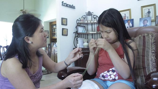 In this photo taken April 22, 2012, Vicky Xiong, left, teaches her daughter Rachel Lor how to do Hmong embroidery at their home in Fresno, Calif. Hmong refugees migrated in large numbers to California's Central Valley after fighting in America's secret war in Laos. (AP Photo/Gosia Wozniacka)