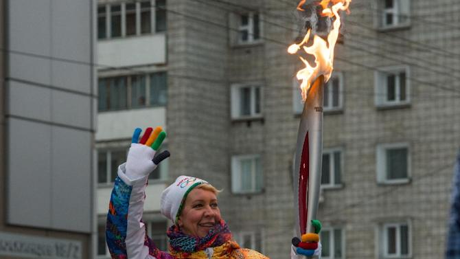 Russian popular entertainer Tatyana Lazareva holds the Olympic torch during the Olympic torch relay in Novosibirsk, about 2,800 kilometers (1,750 miles) east of Moscow, Russia, Friday, Dec. 6, 2013. The 65,000-kilometer (39,000 mile) Sochi torch relay, which started on Oct. 7, is the longest in Olympic history. The torch has traveled to the North Pole on a Russian nuclear-powered icebreaker and has even been flown into space