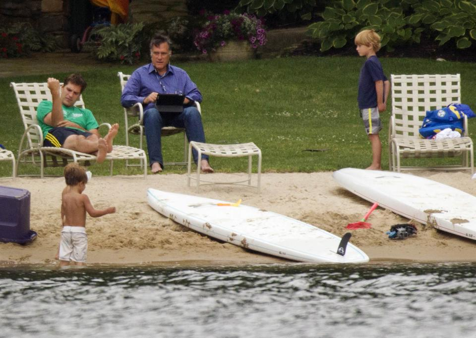 Republican presidential candidate, former Massachusetts Gov. Mitt Romney, right, with his laptop at hand, sits with his family by Lake Winnipesaukee Saturday, July 14, 2012, at his home  in Wolfeboro, N.H.  (AP Photo/Evan Vucci)