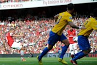 Arsenal&#39;s striker Lukas Podolski (L) scores during their English Premier League football match against Southampton at The Emirates Stadium in north London. Arsenal thrashed bottom of the table Southampton 6-1