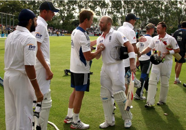 England team players shake hands with batsmen Prior and Bell as they walk off the ground at the end of the first test against New Zealand at the University Oval in Dunedin