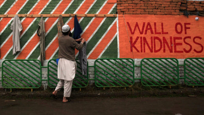 A man takes clothes from wall of kindness in the in Hayatabad locality of Peshawar