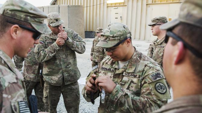 U.S. soldiers from the 3rd Cavalry Regiment smoke cigars as part of Christmas Day celebrations on forward operating base Gamberi in the Laghman province of Afghanistan