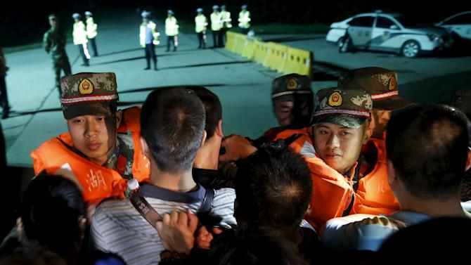 Family members of passengers of a sunken cruise ship push a cordon of paramilitary police as they march toward the site of the sunken ship in the Jianli section of Yangtze River, Hubei province