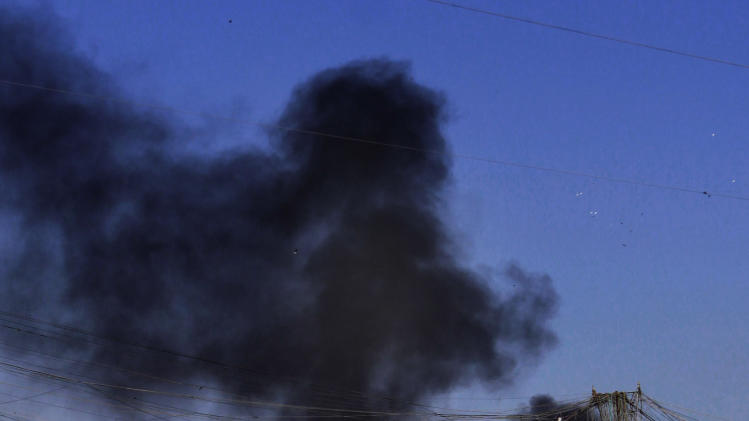 Smoke rises after a car bomb attack in Sadr City, Baghdad, Iraq, Tuesday, March 19, 2013. A wave of apparently coordinated bombings rumbled across the Iraqi capital Tuesday morning, killing and wounding scores of people, police said. (AP Photo/ Karim Kadim)
