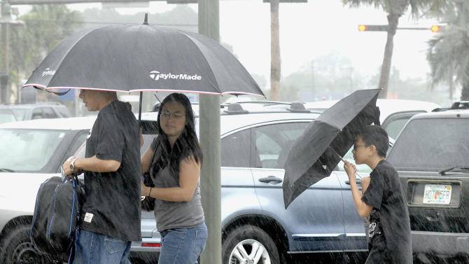 Kenny Ketcham Jr. follows behind his parents Marilou and Kenny Ketcham Sr., while shielding himself from the rain in the Uptown Station shopping center parking lot on Saturday June 9, 2012 in Fort Walton Beach, Fla. (AP Photo/Northwest Florida Daily News, Nick Tomecek)