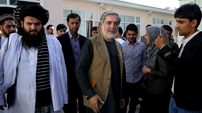 Afghanistan's presidential candidate Abdullah Abdullah, center, leaves after a news conference in Kabul, Afghanistan, Monday, June 23, 2014. Afghanistan's chief electoral officer resigned Monday in a bid to resolve a political crisis over allegations of massive fraud in the runoff presidential vote earlier this month. (AP Photo/Massoud Hossaini)