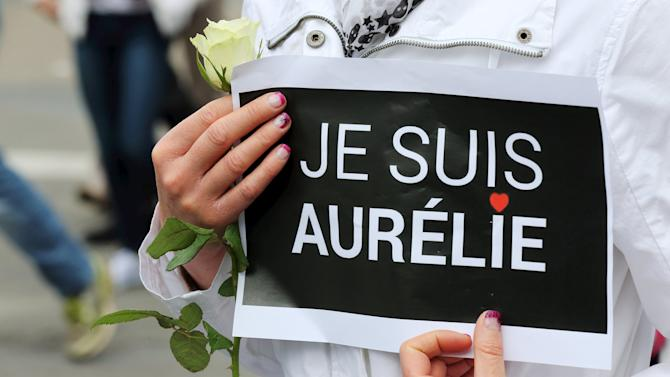 Woman holds a placard during a white march in memory of Aurelie Chatelain, who was found dead last Sunday, on the streets of Caudry