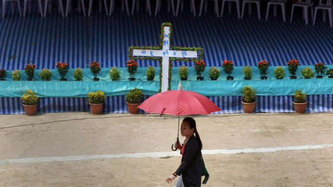 In this photo taken April 12, 2013, a Karen woman walks past a stage to be used for religious services at Mae La refugee camp in Ta Song Yang district of Tak province, northern Thailand. Karen refugees are now facing a future that will dramatically change their constricted but secure, sometimes happy lives. With the end of 50 years of military rule in Myanmar, aid groups are beginning to prepare for the eventual return of one of the world's largest refugee populations, some 1 million in camps and hideouts spread across five countries. (AP Photo/Apichart Weerawong)