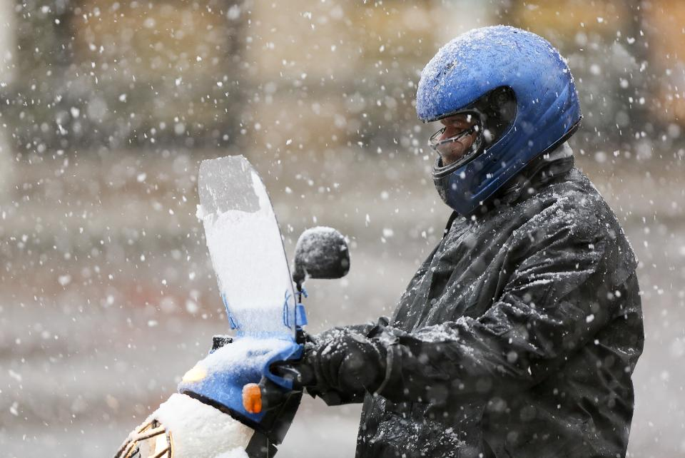 A commuter on a moped heads down Campbell Avenue in heavy snow on Thursday afternoon Jan. 17, 2013 in Roanoke, Va.   Virginia is bracing for the first significant snowstorm of the winter season.  Photo taken 1/17/2013 (AP PHOTO/The Roanoke Times, Kyle Green)