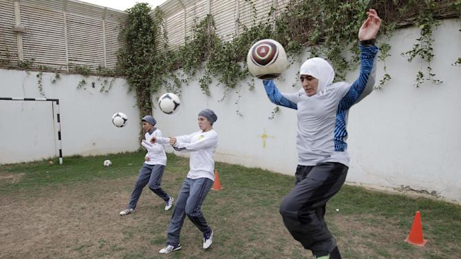 In this May 21, 2012 photo, members of a Saudi female soccer team including captain Rawh Abdullah, left, Rana Al Khateeb, center, and American Mawada Chaballout, right, practice at a secret location in Riyadh, Saudi Arabia. While Olympic leaders and human rights advocates are encouraged by signs that Saudi Arabia may bow to pressure and send female athletes to the Summer Games, women athletes in the ultraconservative kingdom are worried about a backlash at home.(AP Photo/Hassan Ammar)