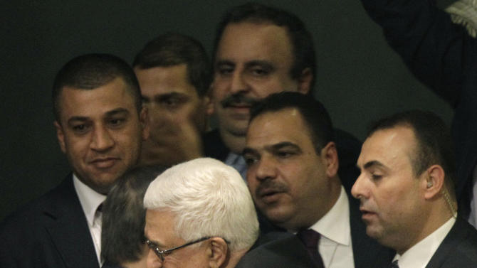 Turklish foreign minister Ahmet Davutoglu embraces Palestinian President Mahmoud Abbas during a meeting of the United Nations General Assembly after a vote on a resolution on the issue of upgrading the Palestinian Authority's status to non-member observer state passed in the United Nations in New York, Thursday, Nov. 29, 2012.  (AP Photo/Kathy Willens)