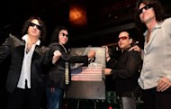 Gene Simmons (2nd L) is last to sign the KISS MONSTER BOOK beside band members Paul Stanley (L), Eric Singer (2nd R) and Thomy Thayer (R) during the release of the largest Rock book ever to be published