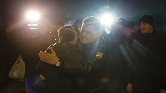 Ukraine's President Petro Poroshenko greets a Ukrainian prisoner-of-war returning home after being exchanged for pro-Russian separatist prisoners, in Kiev
