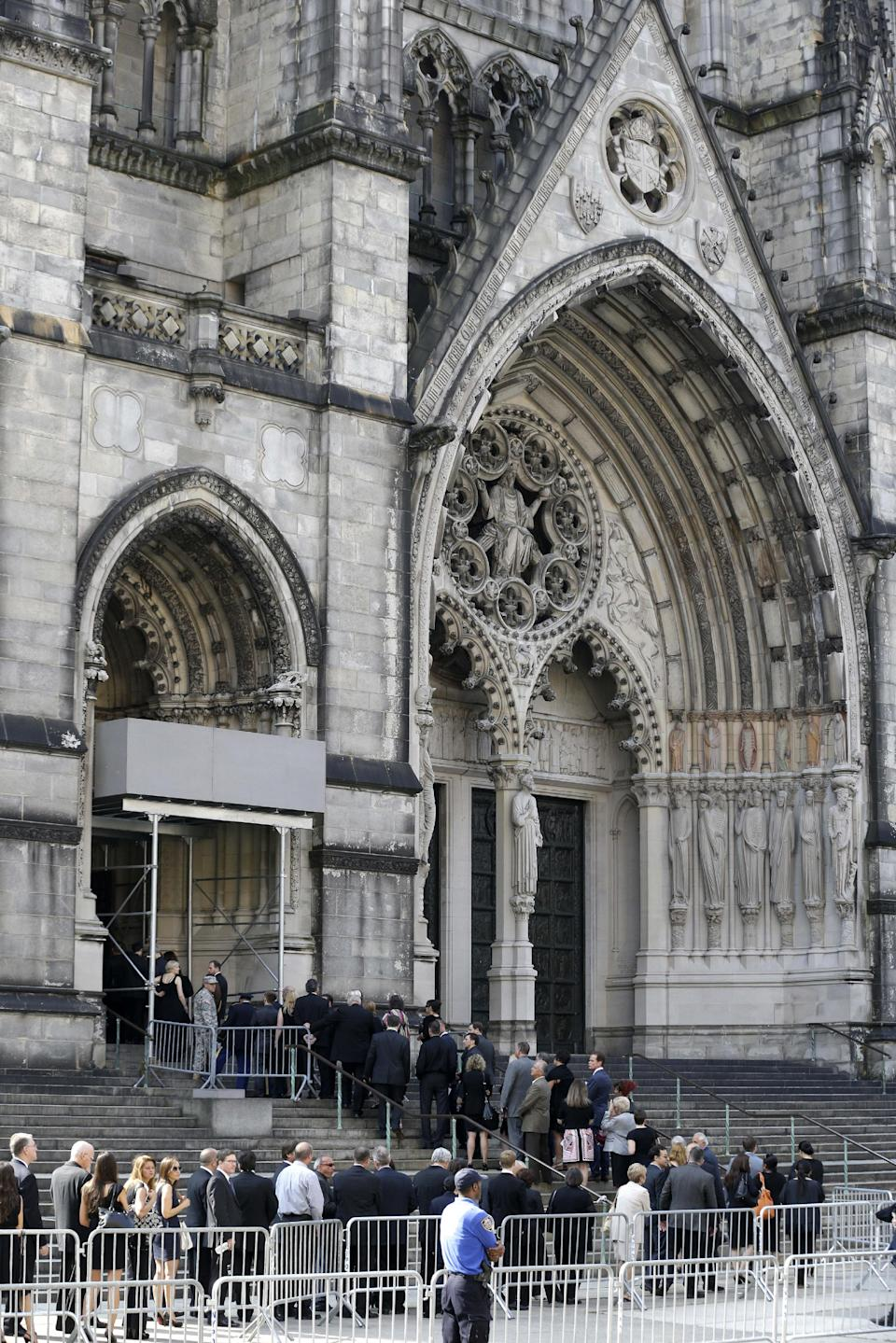 "People walk into Cathedral Church of Saint John the Divine during for funeral services actor James Gandolfini, Thursday, June 27, 2013, in New York. Gandolfini, who played Tony Soprano in the HBO show ""The Sopranos"", died while vacationing in Italy last week. (AP Photo/Julio Cortez)"
