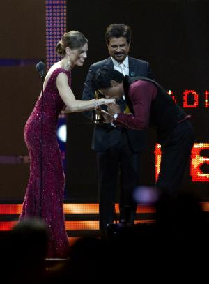 Shah Rukh Khan, right, kisses the hand of actress Hilary Swank, left, while Anil Kapoor stands by, as Khan accepts his award for Best Leading Role Male at the 2011 International Indian Film Academy Awards early Sunday morning, June 26, 2011, in Toronto. (AP Photo/The Canadian Press, Chris Young)