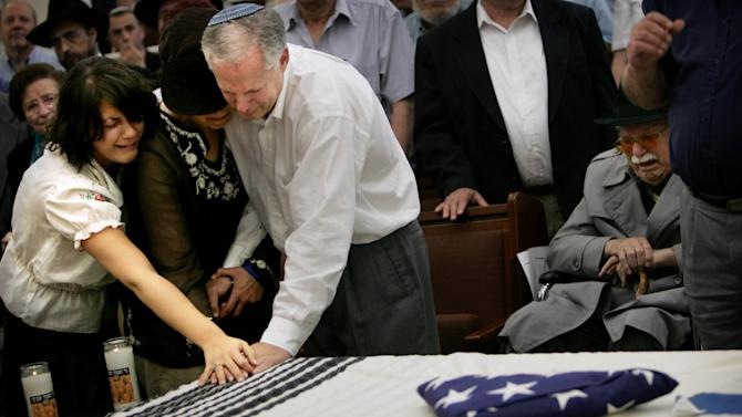 FILE - In this May 15, 2006 file photo, parents of American teenager Daniel Wultz, Tuly, and Cheryl, and his sister Amanda, left, touch his coffin, covered by a Jewish prayer shawl and a folded American flag, given to the family by the U.S. Ambassador in Israel, during a memorial service at a Jerusalem synagogue before transferring his body to the U.S. for burial. Darshan-Leitner is representing 22 families of people who were killed in Palestinian suicide bombings. The families accuse the government-owned Bank of China, through its U.S. branches, of serving as a key conduit in transfers of money to Hamas and Islamic Jihad, Palestinian groups that have killed hundreds of Israelis. The family of Daniel Wultz, a 16-year-old American who was killed in a 2006 suicide bombing in Tel Aviv carried out by Islamic Jihad, is pursuing a separate but related case against the bank. (AP Photo/Oded Balilty, File)