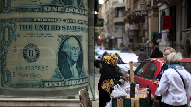 An Egyptian vendor sells nuts in front of a giant poster of a U.S. dollar outside a currency exchange office in Cairo, Egypt, Tuesday, Dec. 25, 2012. As Egypt prepared to release official results from the constitutional referendum, its economy showed increasing signs of distress on Tuesday with worried residents hoarding dollars and fearing that continued political instability will lead to a fast devaluation of the local currency. The Central Bank of Egypt said Tuesday that the U.S. dollar was selling at 6.18 to the Egyptian pound, a spike from the rate of six pounds just two months ago. (AP Photo/Khalil Hamra)