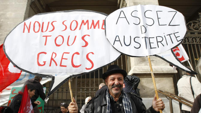 """Worker holds  placards reading """" , We are all Greek, enough austerity"""" , during a demonstration against austerity, in Marseille, southern France,  Wednesday, Nov. 14, 2012.  With rampant unemployment spreading misery in southern Europe and companies shutting factories across the continent, workers around the European Union sought to unite in a string of strikes and demonstrations on Wednesday, with strikes and protests planned in Italy, Greece, Portugal, France and Belgium. (AP Photo/Claude Paris)"""