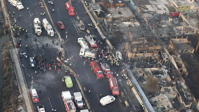Aerial view shows first responders working next to destroyed homes and vehicles after a gas tanker truck exploded on a highway in the Mexico City suburb of Ecatepec early Tuesday, May 7, 2013.  The blast killed and injured dozens, according to the Citizen Safety Department of Mexico State. Officials did not rule out the possibility the death toll could rise as emergency workers continued sifting through the charred remains of vehicles and homes built near the highway on the northern edge of the metropolis. (AP Photo)