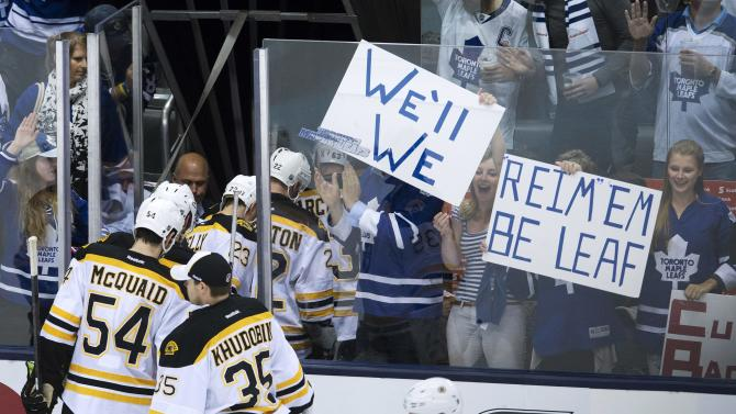 Boston Bruins players leave the ice as Toronto Maple Leafs fans cheers after the Maple Leafs defeated the Bruins to force a game seven during third period NHL hockey playoff action in Toronto on Sunday, May 12, 2013. (AP Photo/The Canadian Press, Nathan Denette)