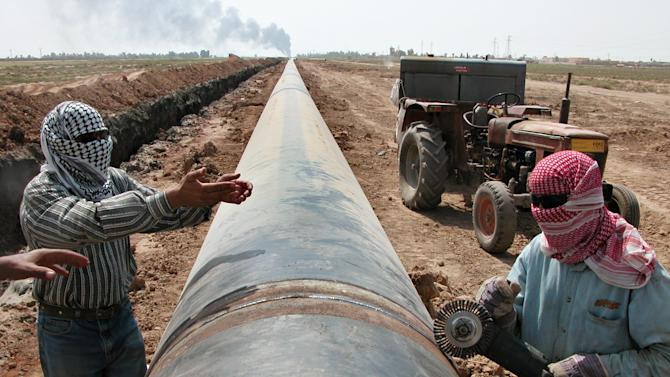 FILE - in this file photo taken on Sept. 6, 2004. Workers lay a new natural gas pipeline after the existing one was targeted by saboteurs near Kirkuk, Iraq. Ten years and $60 billion in taxpayer funds later, Iraq is still so unstable and broken that even its leaders question whether U.S. efforts to rebuild it were worth the cost. (AP Photo/ Yahya Ahmed, File)