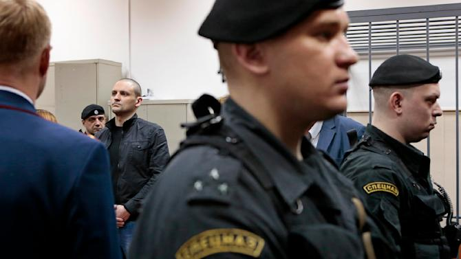 Russian opposition leader Sergei Udaltsov, center back, listens to his sentencing in a courtroom  in Moscow, Russia, Saturday, Feb. 9, 2013. Udaltsov, a top Russian opposition figure, has been placed under house arrest for two months, a move that also bans him from using most forms of communication, including the Internet, telephone and mail. A Moscow court imposed the restrictions Saturday after prosecutors complained he had violated a previous agreement not to leave Moscow. (AP Photo/Mikhail Metzel)
