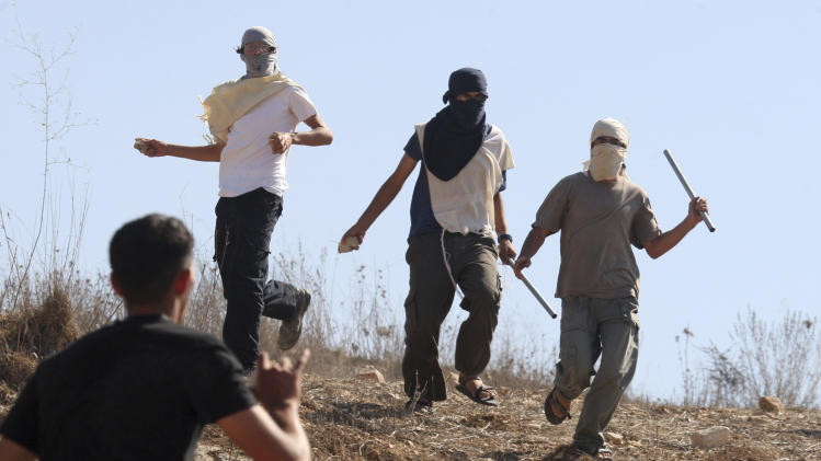 Masked Jewish settlers, top, clash with Palestinians in the West Bank village of Assira al-Kibliya, Tuesday, Sept. 20, 2011. Israeli settlers and Palestinian villagers threw stones at each other Tuesday, a day after Palestinian officials said settlers burned dozens of acres (hectares) of agricultural land and cut down several hundred olive, fig and almond trees. The latest friction came at a particularly sensitive time, with Palestinian President Mahmoud Abbas saying he is determined to seek U.N. recognition this week of a state of Palestine in the West Bank, Gaza and east Jerusalem, areas Israel captured in 1967. (AP Photo/Nasser Ishtayeh)