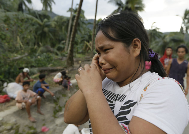 Rosalinda Pasko tearfully breaks the news to a relative of the death of her 2 of her family members at the flash flood-hit village of Andap, New Bataan township, Compostela Valley in southern Philippi