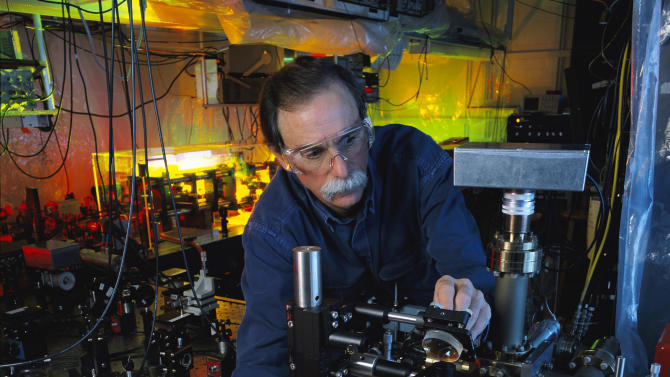 """In this 2003 photo provided by Geoffrey Wheeler and the National Institute of Standards and Technology, physicist David Wineland adjusts an ultraviolet laser beam used to manipulate ions in a high-vacuum apparatus containing an """"ion trap"""" used to demonstrate the basic operations required for a quantum computer. Wineland and Serge Haroche of France shared the 2012 Nobel Prize in physics Tuesday, Oct. 9, 2012 for inventing methods to observe the bizarre properties of the quantum world, research that has led to the construction of extremely precise clocks and helped scientists take the first steps toward building superfast computers. (AP Photo/NIST, Geoffrey Wheeler)"""
