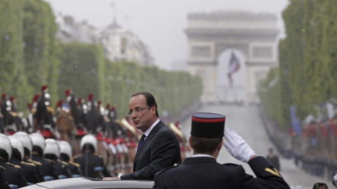 New French President Francois Hollande looks out of his car as he rides up the Champ-Elysses avenue after the presidential handover ceremony, Tuesday, May 15, 2012 in Paris.   Hollande became president of France on Tuesday in a ceremony steeped in tradition, taking over a country with deep debts and worried about Europe's future and pledging to make it a fairer place. The Arc de Triomphe is seen  in the background. (AP Photo/Michel Euler)