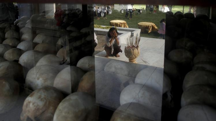 "A woman is reflected in a glass pane as she prays with incense sticks during a gathering at a memorial stupa at Choeung Ek, a ""Killing Fields"" site located on the outskirts of Phnom Penh"