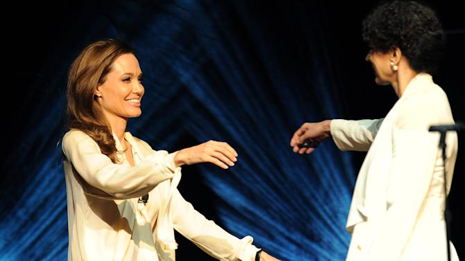 "Angelina Jolie, left, director of the upcoming film ""Unbroken,"" is greeted onstage by Universal Pictures Chairman Donna Langley during the Universal Pictures presentation at CinemaCon 2014 on Tuesday, March 25, 2014 in Las Vegas. (Photo by Chris Pizzello/Invision/AP)"