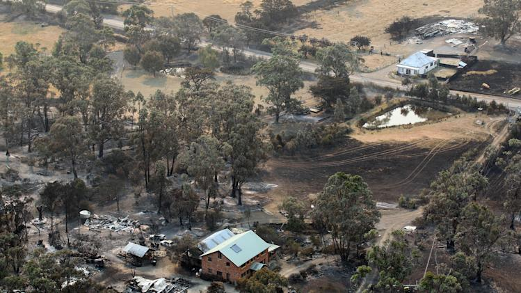 A building sits among the charred remains of properties following a wildfire near Dunalley, east of the Tasmanian capital of Hobart, Australia, Saturday, Jan. 5, 2013.  Australian officials battled a series of wildfires amid scorching temperatures across the country on Saturday, with one blaze destroying dozens of homes in the island state of Tasmania. (AP Photo/Chris Kidd, Pool)