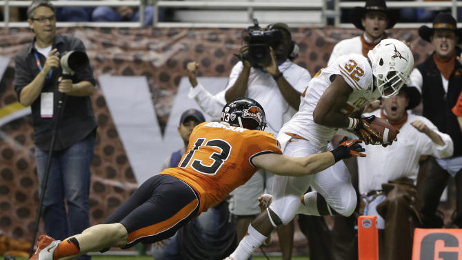 Texas' Johnathan Gray (32) scores a touchdown as Oregon State's Rueben Robinson (13) defends during the fourth quarter of the Alamo Bowl NCAA football game, Saturday, Dec. 29, 2012, in San Antonio.  Texas won 31-27. (AP Photo/Eric Gay)