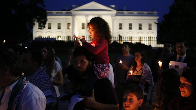 Wafa, 3, sits on the shoulders of her father Mahmoud Abuarqoub, a Palestinian American from Baltimore, Md., as demonstrators hold a vigil for the victims of the fighting between Israel and Hamas in Gaza in front of the White House in Washington, Wednesday, July 30, 2014. (AP Photo/Charles Dharapak)
