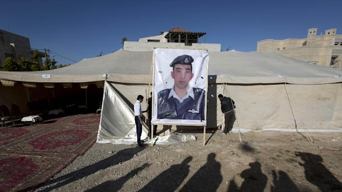 A banner with a picture of Jordanian pilot, Lt. Muath al-Kaseasbeh, who is held by the Islamic State group militants, is being raised by workers near a tent prepared for receiving supporters, in Amman, Jordan, Friday, Jan. 30, 2015. The fates of a Japanese journalist and Jordanian military pilot were unknown Friday, a day after the latest purported deadline for a possible prisoner swap passed with no further word from the Islamic State group holding them captive. (AP Photo/Nasser Nasser)