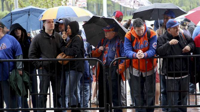 Fans stand in the rain while looking through the gates into Citi Field after the baseball game between the New York Mets and San Francisco Giants was postponed due to weather, Sunday, April 22, 2012, in New York. A spring nor'easter along the East Coast is expected to bring rain and heavy winds and even snow in some places as it strengthens into early Monday, a punctuation to a relatively dry stretch of weather for the Northeast. (AP Photo/Seth Wenig)