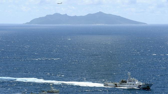 FILE - In this Sept. 14, 2012 file photo, the Chinese surveillance ship Haijian No. 51, left, and a Japan Coast Guard vessel sail near disputed islands called Senkaku in Japan and Diaoyu in China, seen in background, in the East China Sea. Japanese were voting Sunday in parliamentary elections that were expected to put the once-dominant conservatives back in power after a three-year break — and bring in a more nationalistic government amid tensions with big neighbor China. Japan's largest opposition Liberal Democratic Party leader Shinzo Abe in particular has taken a tough stance toward Beijing in the election campaign amid a simmering dispute over the tiny islands that are controlled by Japan but also claimed by China and Taiwan. (AP Photo/Kyodo News, File) JAPAN OUT, MANDATORY CREDIT, NO LICENSING IN CHINA, HONG KONG, JAPAN, SOUTH KOREA AND FRANCE