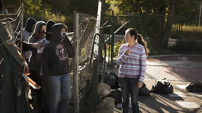 A woman asks for a permission to enter Complutense University as students block the entrance with a barricade during a student strike to protest against the government education reform and cutbacks in grants and staffing in Madrid, Spain, Thursday, Oct. 23, 2014. (AP Photo/Andres Kudacki)