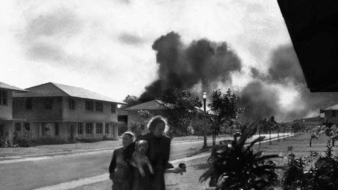 "FILE - In this Dec. 7, 1941 file photo, officers' wives head to their quarters after investigating the sound of an explosion and seeing smoke in distance in Pearl Harbor, Hawaii. The two heard neighbor Mary Naiden, then an Army hostess who took this picture, exclaim ""There are red circles on those planes overhead. They are Japanese!"" (AP Photo/Mary Naiden)"