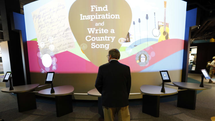 In this April 10, 2014, photo, a visitor looks at an exhibit in a new section of the Country Music Hall of Fame and Museum in Nashville, Tenn. A $100 million expansion has added more than 200,000 square feet of space to the existing building. (AP Photo/Mark Humphrey)