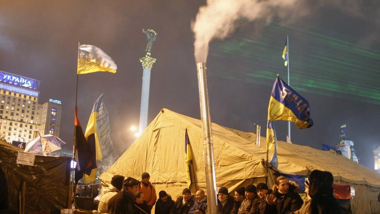Pro-European integration protesters warm themselves by a fire at Independence Square in Kiev