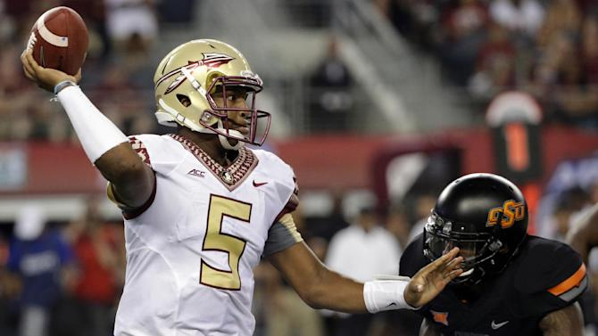 In this Aug. 30, 2014, file photo, Florida State quarterback Jameis Winston (5) passes under pressure from Oklahoma State linebacker Josh Furman (14) during an NCAA college football game  in Arlington, Texas. Things didn't come nearly as easy for the Heisman winner, and the FSU offense will need to play much better if the Seminoles are to win the first College Football Playoff