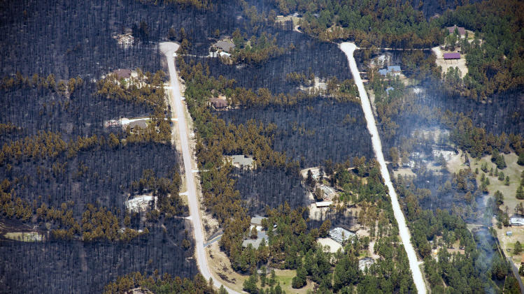 Blackened areas defines the path of a wildfire that destroyed some homes and left others untouched in one neighborhood in the densely wooded Black Forest area northeast of Colorado Springs, Colo., Thursday, June 13, 2013. More than 350 homes have been lost in what is now the most destructive wildfire in Colorado history, surpassing last year's Waldo Canyon fire, which burned 347 homes, killed two people and led to $353 million in insurance claims. (AP Photo/John Wark)