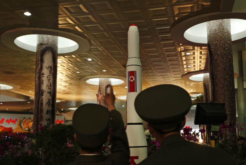 North Korean soldiers look at a model of a rocket during a flower show to celebrate 100 years since the birth of North Korean founder Kim Il Sung in Pyongyang, North Korea, Tuesday, April 17, 2012. (AP Photo/Vincent Yu)