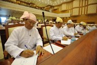 Myanmar MPs sit behind microphones during a session of parliament's lower house in Yangon on Tuesday. Myanmar has fired the starting gun in the process of liberalising its communications networks in a move that could finally bring mobile and Internet access to the masses and drive international investment