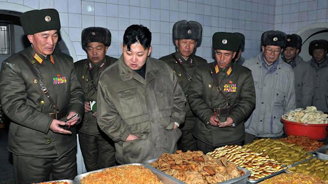 FILE - In this undated file photo released by the Korean Central News Agency and distributed in Tokyo by the Korea News Service, North Korean leader Kim Jong Un, third from right, looks at food items as he inspects a military unit at an undisclosed location in North Korea. For the outside world, North Korea's message is largely doom and gloom: bombastic threats of nuclear war, amateur-looking videos showing U.S. cities in flames, digitally altered photos of military drills. But a domestic audience gets a parallel and decidedly softer dose of propaganda - and one with potentially higher stakes for the country's young leader. (AP Photo/KCNA via KNS, File)