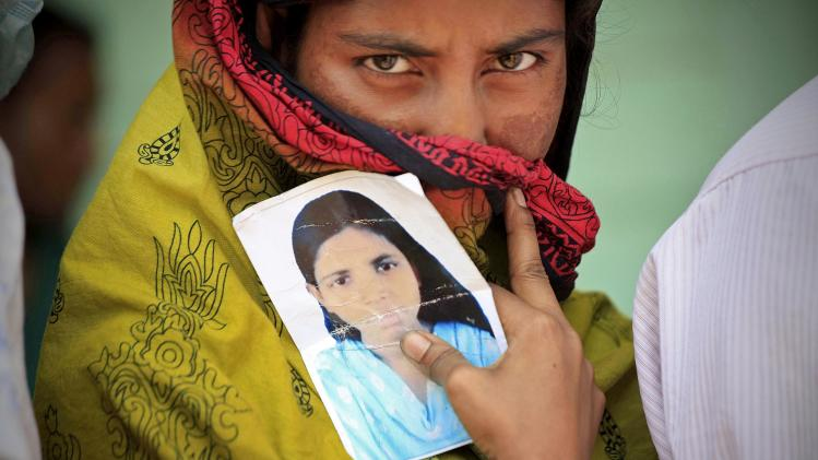 A woman holds a photo of her missing sister after a garment factory building collapsed last week in Savar near Dhaka, Bangladesh, Friday May 3, 2013. Authorities suspended the mayor of the suburb of Savar, where the building was located, and arrested an engineer who called for the building's evacuation last week but was also accused of helping the owner add three illegal floors to the eight-story structure. (AP Photo/Ismail Ferdous)